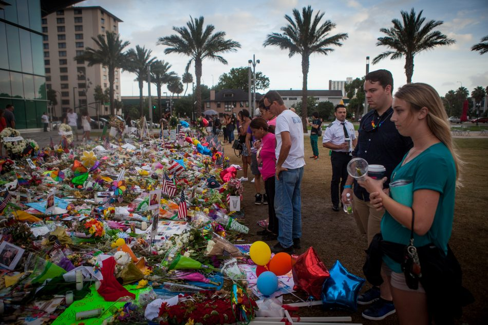 People pay respects to the vicitms of the Pulse massacre infront of the Dr. Phillips Center for the Performing Arts on June 19, 2016.